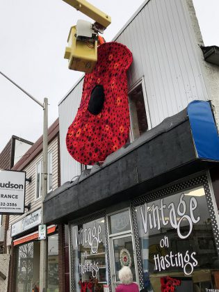 The hanging of the 11-foot poppy at Vintage on Hastings in Bancroft. (Photo: Barb Shaw)