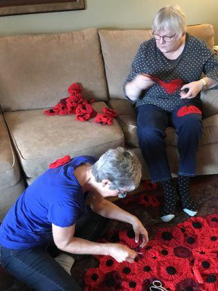 Hospice volunteers Joyce Close and Elizabeth Jewell work on stitching all the poppies together for the 2018 installation.  (Photo: Barb Shaw)