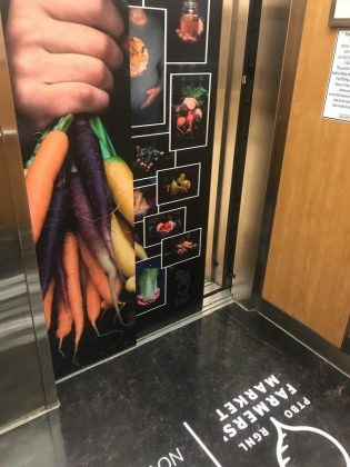 Even the marketing for the Peterborough Regional Farmers' Market is local: local marketing company 79 Dev created the elevator wrap that reminds Peterborough Square patrons all week of the Saturday indoor market, and the market logo (seen in part on the floor) was designed by local agency Hatch Creative. (Photo: Barb Shaw / kawarthaNOW.com)