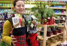 Store associate Tabetha Graham showcases many of the green stocking stuffers under $25 offered at the GreenUP Store, where all items are carefully sourced to meet high environmental standards.
