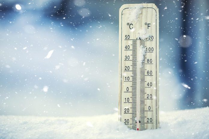 Extreme cold shown on thermometer in snow