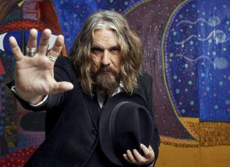 "Veteran Canadian musician Tom Wilson, pictured in front of some of his paintings, accidentally discovered seven years ago both that he was adopted and his birth parents were Indigenous, leading him to write his critically acclaimed autobiography ""Beautiful Scars"" in 2017. Wilson, who performs as Lee Harvey Osmond, is releasing his latest album ""Mohawk"" on January 25, 2019. He will be performing songs from the new record and more at his February 2nd concert at the Market Hall Performing Arts Centre in downtown Peterborough, sponsored by kawarthaNOW. (Photo: Marta Hewson)"