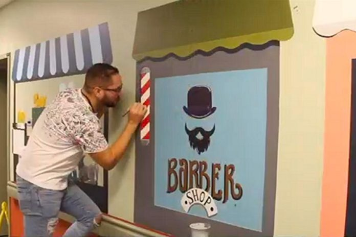 Miguel, project coordinator with the Art School of Peterborough, works on a mural. (Screenshot from PRHC video)