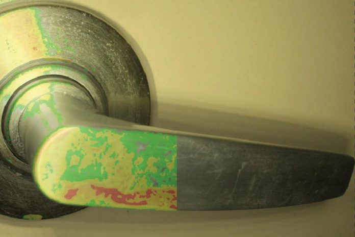 The left side of photo shows actual microbial contamination detected on a door handle by  Charlotte Products Ltd.'s OptiSolve Pathfinder environmental monitoring system and optical sensor technology, with the right side of the photo showing how the door handle looks to the naked eye. (Photo:  Charlotte Products Ltd.)
