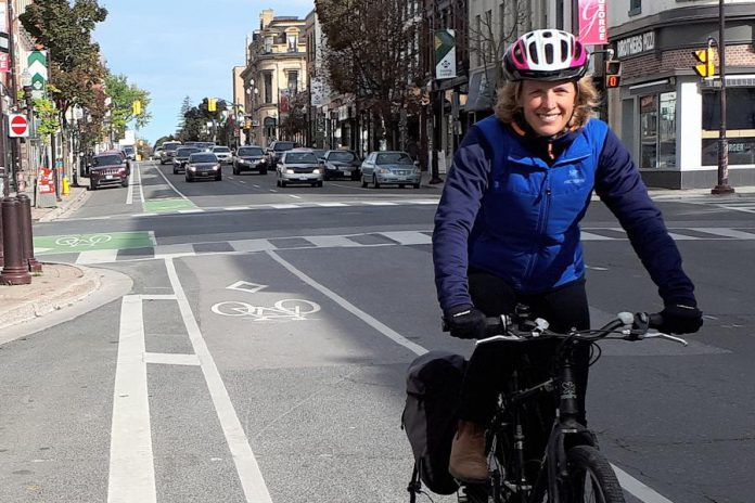 Jaime Akiyama, GreenUP's Transportation and Urban Design Program Coordinator, rides her bike along the George Street bike lane in Peterborough, with her panniers loaded up after shopping downtown. (Photo courtesy of GreenUP)