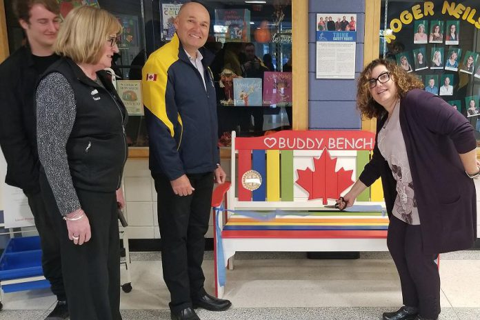 Roger Neilson Public School principal Denise Humphries (right) cuts the ribbon on the Rotary Buddy Bench as Nate Loch, Rotarian Donna Geary, and Kawartha Rotary Club president Brian Prentice look on. Geary and her son Nate initiated the Rotary Buddy Bench program in Peterborough in 2017, donating a bench to St. Catherine's Catholic Elementary School in Peterborough. The bench is intended to to reduce loneliness and foster friendships on the playground. (Photo courtesy of Rotary Club of Peterborough Kawartha)