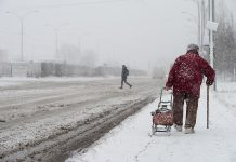 Older woman walking in a winter snow storm
