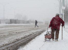 Older woman walking in a winter snow storm
