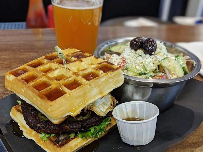 Port Hope's Olympus Burger is renowned for its creative burgers, like the Dionysus with a black bean patty, jalapeños, fried egg, lettuce, local maple syrup, and waffles instead of a regular bun. (Photo: Olympus Burger)