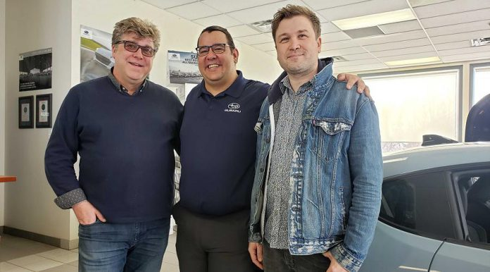 Peterborough Folk Festival board chair Malcolm Byard (left) and vice chair and artistic director Ryan Kemp (right) with Phillip Jolicoeur, sales and marketing specialist at Peterborough Subaru, during the announcement on  March 19, 2019 at the car dealership's showroom on Chemong Road that Peterborough Subaru is sponsoring the 2019 summer festival. (Photo: Jeannine Taylor / kawarthaNOW.com)
