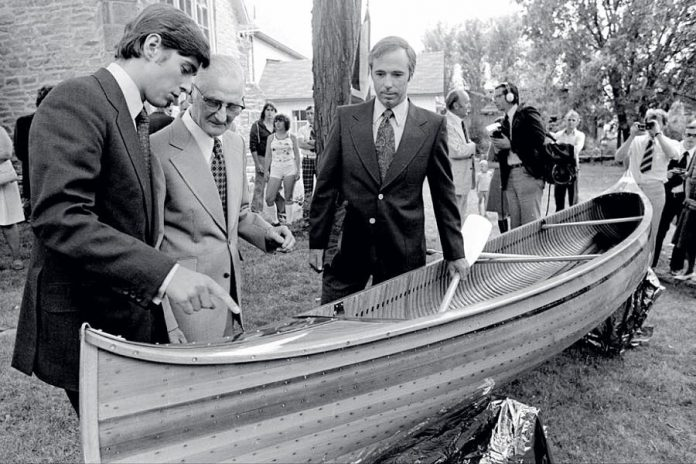 A 17-year-old Prince Andrew (left) receiving his handmade cedar-strip canoe from 70-year-old master builder Walter Walker (centre) in Lakefield on June 15, 1977. On the right is Terry Guest, headmaster of Lakefield College School which Prince Andrew attended from January to June in 1977. Prince Andrew donated the canoe  to The Canadian Canoe Museum's collection in 2004. (Photo: Michael Peake)