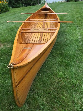 The 16-foot cedar-strip canoe constructed by renowned Lakefield boat-builder Walter Walker, along with a pair of hand-carved cherry paddles, will be auctioned off to the highest bidder at the Campfires & Cocktails fundraiser at  The Canadian Canoe Museum on May 4, 2019. Bids by proxy will also be accepted until May 3rd. (Photo courtesy of The Canadian Canoe Museum)
