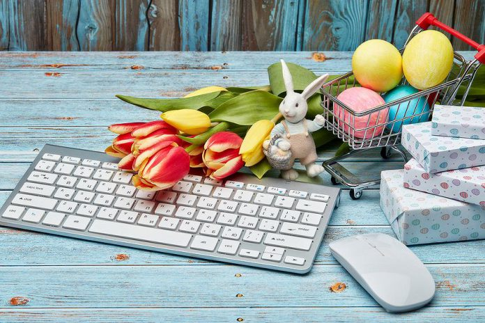 Colored Easter eggs in a miniature shopping cart, gift boxes, tulips and computer keyboard and mouse on a wooden background.