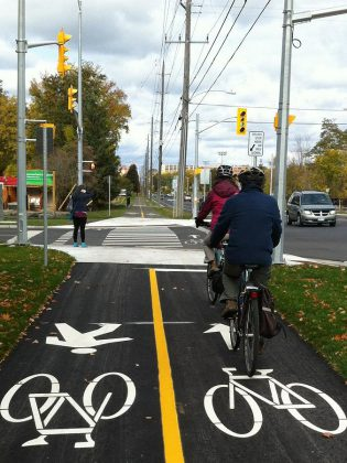 People ride bikes and walk along the multi-use trail on Ashburnham Drive, Peterborough. Log your walking, biking, transit, and carpooling trips this May to win prizes.  (Photo courtesy of GreenUP)