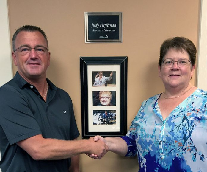 Kim Appleton in 2016, when she was chair of the board of Community Futures Peterborough, welcoming Jeff Day as the organization's new executive director at the time. In the background is the memorial boardroom for Judy Heffernan, who served at general manager for 17 years. Before Heffernan passed away suddenly in 2013, she encouraged Appleton to serve on the male-dominated board. (Photo: Community Futures Peterborough)