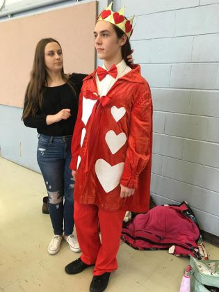 """Miranda Steiginga helping Ben Stevenson with his costume as The King of Hearts during a rehearsal of  """"Alice @ Wonderland: The Musical"""". (Photo:  Jim Mills)"""