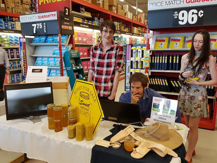 Nathan Clifford (left) was one of nine young entrepreneurs who participated in the 2018 Summer Company program delivered locally by the Peterborough & the Kawarthas Business Advisory Centre. In his business called Green Improvements, Nathan developed a computer-based system to enable beekeepers to monitor the health of their hives. A showcase of the student-run companies was held at Staples in Peterborough as part of the province-wide Summer Company-Staples Youth Entrepreneurship Day on July 4, 2018. (Photo: Amy Bowen / kawarthaNOW.com)