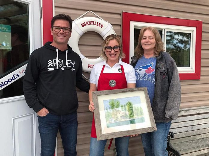 "Yannick Bisson, who portrays William Murdoch on CBC television's award-winning series ""Murdoch Mysteries"", and his wife Shantelle Bisson at Shantilly's Place (formerly West Bay Narrows Marina) on Chandos Lake in North Kawarthas. Also pictured is artist Terri Butler (right), who gifted the couple a painting of the original West Bay Narrows Marina. The Bissons, who have a cottage on the lake, purchased the marina in 2018. Shantilly's Place opened for the summer season on May 17, 2019. (Photo: Shantilly's Place)"