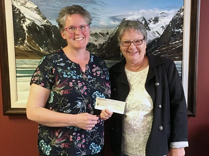Louise Racine (right), founder and committee chair of International Women's Day Conference Peterborough, presents Jennifer DeBues, director of operations and granting at Community Foundation of Greater Peterborough, with a $650 cheque for The Judy Heffernan Award fund on June 20, 2019. (Photo: John Good / Community Foundation of Greater Peterborough)