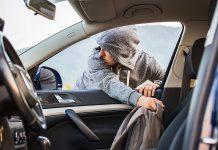 Thief stealing bag through open window of car