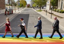 Representatives from community groups, the Cobourg Police Service, and the Town of Cobourg mimic the famous cover of The Beatles' Abbey Road album during the celebration of the new rainbow crosswalk at King Street West and Second Streets in downtown Cobourg. The crosswalk, which was unveiled during Pride Month in Cobourg, will remain in place for the rest of the summer. (Photo: Town of Cobourg / Facebook)