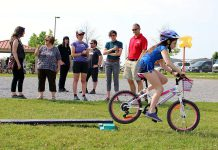 A Grade 5 student from Monsignor O'Donahue Catholic Elementary School demonstrates her riding skills on the Bike Playground, while funders and partners of the Pedal Power program look on. (Photo: Karen Halley)