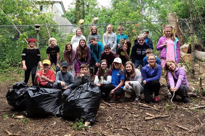 Grade 6 students at Kawartha Heights Public School in Peterborough pose with bags full of invasive garlic mustard, after pulling the plants from their schoolyard last year. (Photo: GreenUP)