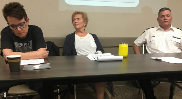 There were no happy faces among the three speakers at a public meeting on the opioid crisis on June 12, 2019 at the Lions' Community Centre in Peterborough. From left to right: Whitepath Consulting and Counselling Services owner Peggy Shaughnessy, PARN  executive director Kim Dolan, and Peterborough Deputy Police Chief Tim Farquharson.  Around 100 people showed up for the meeting. (Photo: Paul Rellinger / kawarthaNOW)