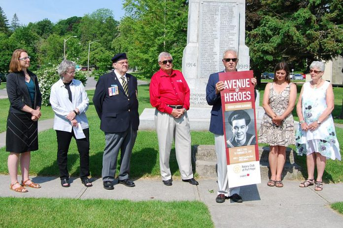 Port Hope Rotary Club president Bob Wallace presents a mock-up of the Avenue of Heroes banners at the Memorial Park cenotaph on June 19, 2019. The banners will be installed along streets in downtown Port Hope this fall. Pictured on the mock-up is a photo of George Narraway, a World War II veteran and the late father of Kevin Narraway, a manager in Port Hope's marketing and tourism department, which is leading the banner design. (Photo: April Potter / kawarthaNOW.com)
