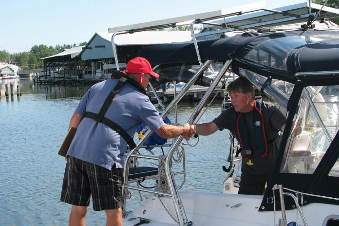 A volunteer with the Peterborough Power and Sail Squadron prepares to board a boat to conduct a recreational vessel courtesy check. Squadron members conduct several such checks each summer at marinas throughout Peterborough and the Kawarthas. (Photo courtesy of Peterborough Power and Sail Squadron)