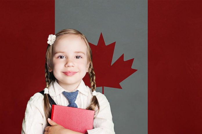 A young female student in front of the Canadian flag