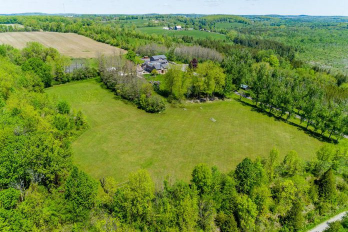 An aerial view of 124 Lily Lake Road, which sits on 100 acres or forest and fields, providing unparalleled privacy.