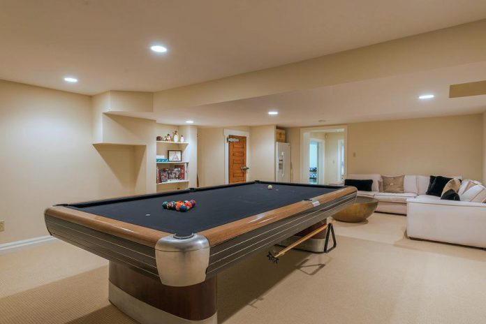 The bright open-concept finished basement has a spacious game room with a vintage art deco pool table, included in the sale.