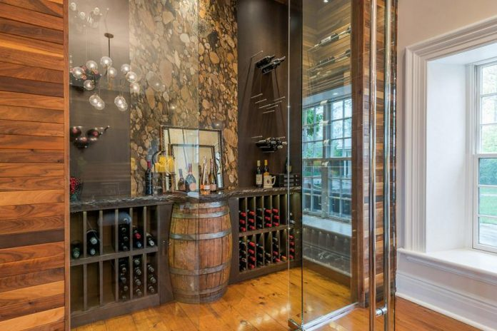 The open glass temperature-controlled wine room is open to the kitchen and family room and features a signature a river rock granite wall in the middle and an oak barrel display table.