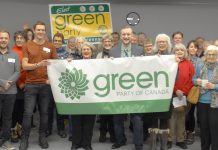 Brock Grills, pictured here (under clock, holding banner) after winning the Peterborough-Kawartha federal Green Party nomination on February 25, 2019, has stepped down as the candidate for personal reasons. (Photo: Peterborough-Kawartha Federal Green Party Association )