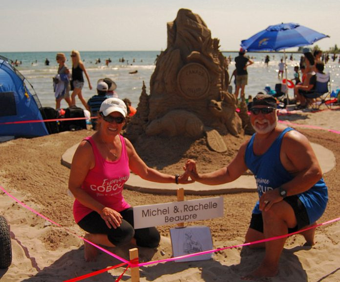 Master sculptors Michel Beaupre and Rachelle Rocheleau from Quebec pose in front of their sculpture at the Cobourg Sandcastle Festival on August 3, 2019. (Photo: April Potter / kawartha