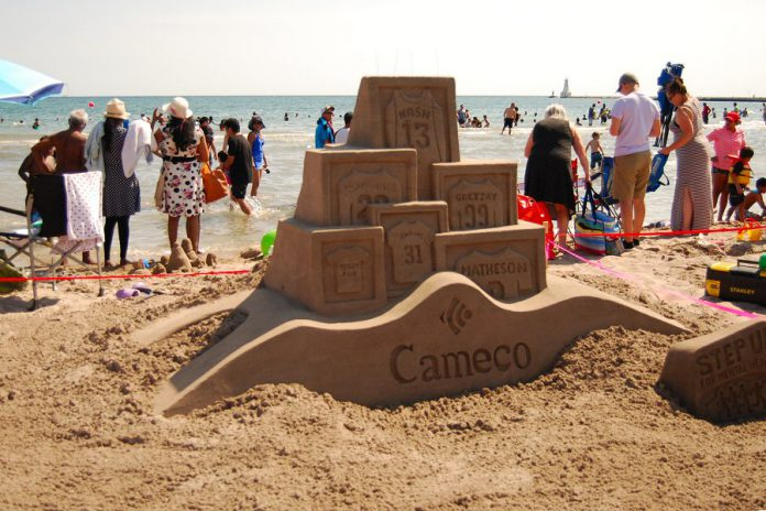 At the Cobourg Sandcastle Festival on August 3, 2019 at Victoria Beach in the Town of Cobourg, master sculptor Dale Andrews created the sports-themed design for corporate sponsor Cameco, showcasing the jerseys of prominent athletes on Canadian sports teams and celebrating our country's love of sport.   (Photo: April Potter / kawarthaNOW.com)