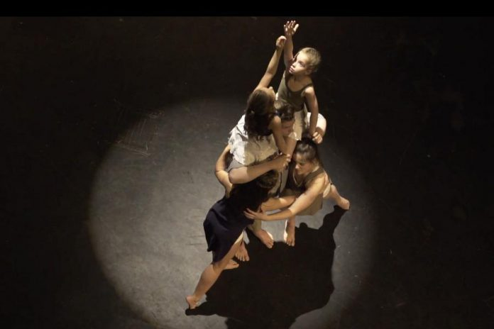 "The film's title ""Surfacing"" refers to the eventual journey towards healing of writer Frank Flynn and his two daughters (represented here as their younger and older selves) following the loss of their mother to suicide. Pictured are dancers Lilly Manning, Laine Andrews, Oliver Moriarty, Madison Sheward, and Kate Bemrose. (Screenshot)"