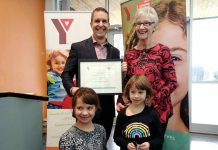YMCA of Central East Ontario board chair John Mastorakos presents Peterborough educator and activitist Rosmary Ganley with the 2018 YMCA Peace Medal on November 23, 2018 as Ganley's grandaughters Ava and Emma look on. Nominations for the 2019 Peace Medal are now open. (Photo: YMCA of Central East Ontario / Facebook)