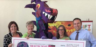 Pterborough Regional Health Centre (PRHC) Foundation president and CEO Lesley Heighway (left) and PRHC Foundation board chair Gord McFarland (right) accept a cheque for $241,738.54 from incoming Peterborough's Dragon Boat Festival chair Gina Lee, festival dragon Bill Thornton (in costume), and outgoing festival chair Michelle Thornton on September 18, 2019 at PRHC. (Photo courtesy of Peterborough's Dragon Boat Festival)