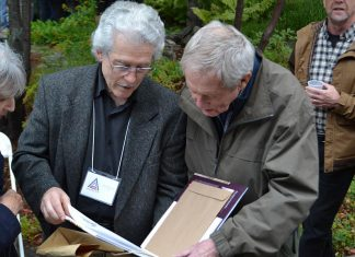 """Renowned Canadian wildlife artists Michael Dumas and Robert Bateman in Algonquin Park at the 75th anniversary fundraiser for the Algonquin Wildlife Research Station on September 14, 2019, where Bateman was presented with the 2019 Algonquin Park Legacy Award by Dumas, the inaugural recpient of the award from the Algonquin Art Centre. Dumas also presented Bateman with a limited edition of """"The Artists of Kawartha"""", the fourth art book in a series designed and published by Algonquin-area publisher Andrea Hillo. (Photo courtesy of Andrea Hillo)"""