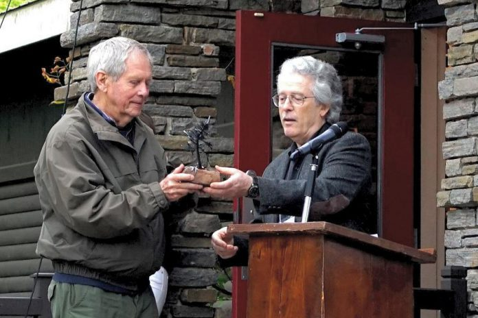 Robert Bateman accepting the 2019 Algonquin Park Legacy Award from Michael Dumas, who was the inaugural recpient of the award in 2018, at a 75th anniversary fundraiser for the Algonquin Wildlife Research Station at the Algonquin Art Centre in Algonquin Park on September 14, 2019.  (Photo: Linda Sorensen / Facebook)