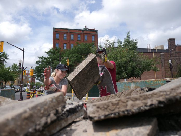 The Engage Engineering team lifting asphalt with gusto in preparation for creating a new garden outside Euphoria Wellness Spa in downtown Peterborough. (Photo courtesy of GreenUP)