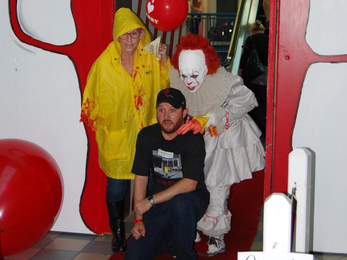 "Adam Pearson, owner of Queenies Bake Shop, at a special screening of ""IT Chapter Two"" at Cobourg's Rainbow Cinemas in Northumberland Mall on September 5, 2019, along with costumed fans Laurie Statt and Melindah Knott. Pearson, with the help of local artists and volunteers, created a large-scale art project for the screening which also raised funds for the Northumberland Fare Share Food Bank. Pearson, whose Port Hope business benefited from the production of the film, appears as an extra who get shoved out of the way by actor James McAvoy during the film's funhouse scene. (Photo: April Potter / kawarthaNOW.com)"
