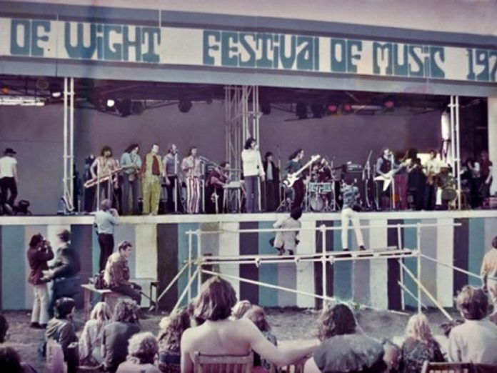 Lighthouse turned down an invitation to perform at Woodstock in 1969, but the following year they played the even bigger Isle of Wight Festival in England, sharing the stage with the likes of Jimi Hendrix, The Doors, The Who, The Moody Blues, Joni Mitchell, and many more. From left: Keith Jollimore, Howard Shore, Pete Pantaluk, Bruce Cassidy, Larry Smith, Paul Hoffert, Bob McBride, manager Vinnie Fusco standing at back, Louis Yachnin, Skip Prokop, Ralph Cole, Don DiNovo, Paul Armin, and Dick Armin. (Photo courtesy of Hoffert Communications)