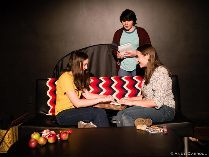 Max (Samuelle Weatherdon) and Billie (Aimee Gordon) experiment with Ouija board on Halloween as  Regi (Emily Keller) looks on. (Photo: Andy Carroll)
