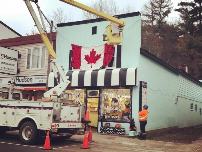 Staff from the Town of Bancroft assisted with the installation of the hand-crafted poppy flag on the outside of the second floor of Vintage on Hastings in Bancroft. (Photo: Barb Shaw)