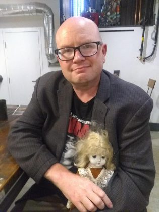 "Sam Tweedle spending some quality time with one of Kathryn Bahun's dolls. ""I've had it haunt my dreams,"" Sam writes. (Photo courtesy of Sam Tweedle)"