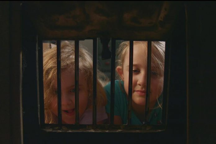 Seven-year-old Zoe (Zoe Hayes, right) thinks her her bothersome five-year-old sister Emma (Emma Hayes) is always making things up, so when Emma reports there's a monster hiding in the fieldstone walls of their basement, Zoe doesn't believe her ... at first.  (Screenshot courtesy of Michael Hayes and Brendan Fell)