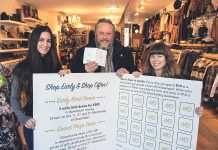 "Terry Guiel, executive director of the Peterborough Downtown Business Improvement Area (DBIA), and Wendy Gillis and Malissa Almond hold up a giant Holiday Shopping Passport as they celebrate the launch of the annual downtown shopping program on November 12, 2019 at Save Our Soles (385 George St. N., Peterborough), one of the 148 businesses and organizations in downtown Peterborough participating in the program. Shoppers get a stamp every time they spend $10 at one of the participating locations, and completed passports are entered into a draw for ""downtown money"" that can be redeemed at participating locations. (Photo courtesy of Peterborough DBIA)"